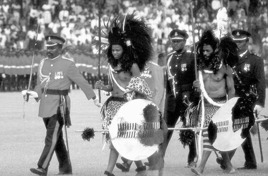 Szváziföld királya és fia napjainkban, hagyományos ornátusban, testőreivel
