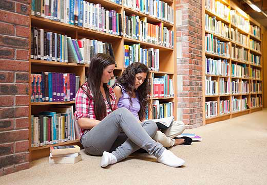 female_students_with_a_book_in_a_library-wide
