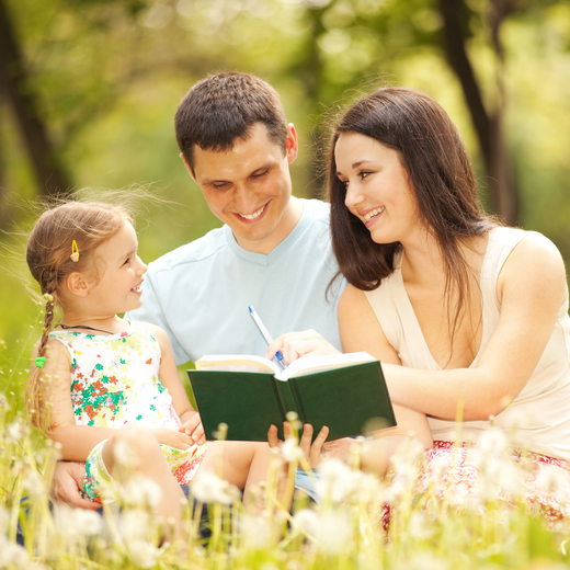 happy_mother_father_and_daughter_read_a_book_in_th