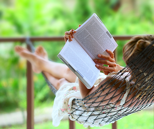 young_woman_reading_a_book_lying_in_hammock-wide