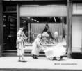 Kisgyermekes család sétál egy belvárosi kirakat előtt